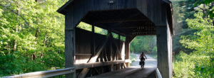 Header-person-riding-bike-on-covered-bridge